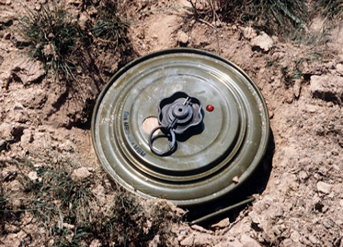 A landmine partly buried in sand